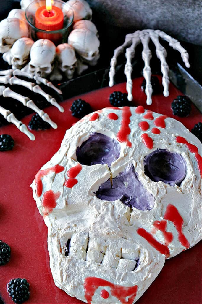 A vertical overhead closeup of a Swiss Meringue Skull with strawberry jelly blood and marshmallow teeth.