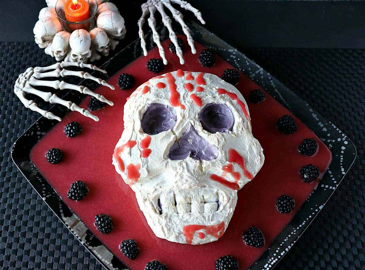 Overhead photo of a Swiss meringue skill with berry puree and skeleton hands.