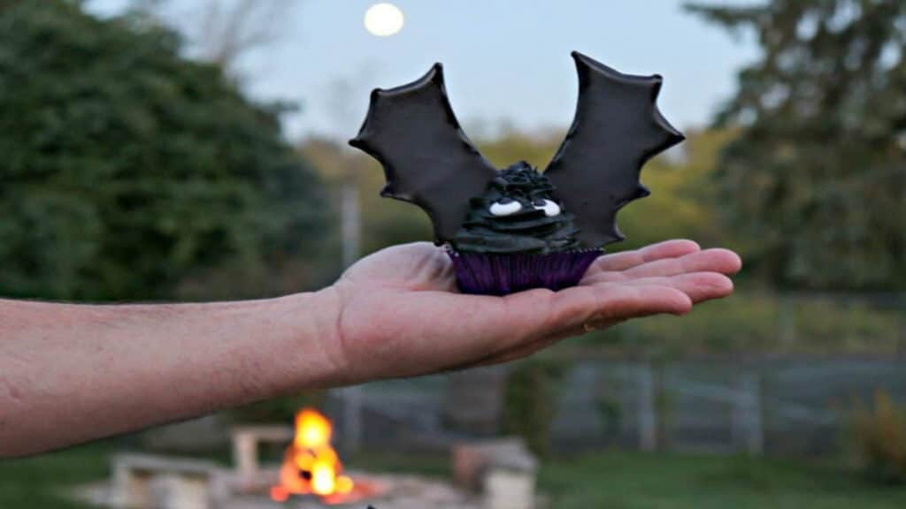 A hand holding a batwing cupcake with a fire and a full moon in the background