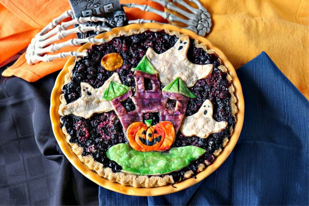 Overhead photo of a boo berry pie with ghosts and a haunted house.