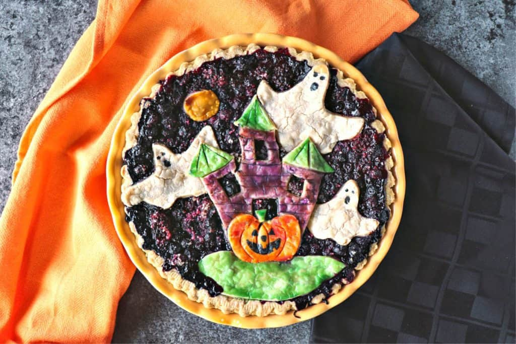 Overhead photo of a Halloween pie with orange and black napkins.