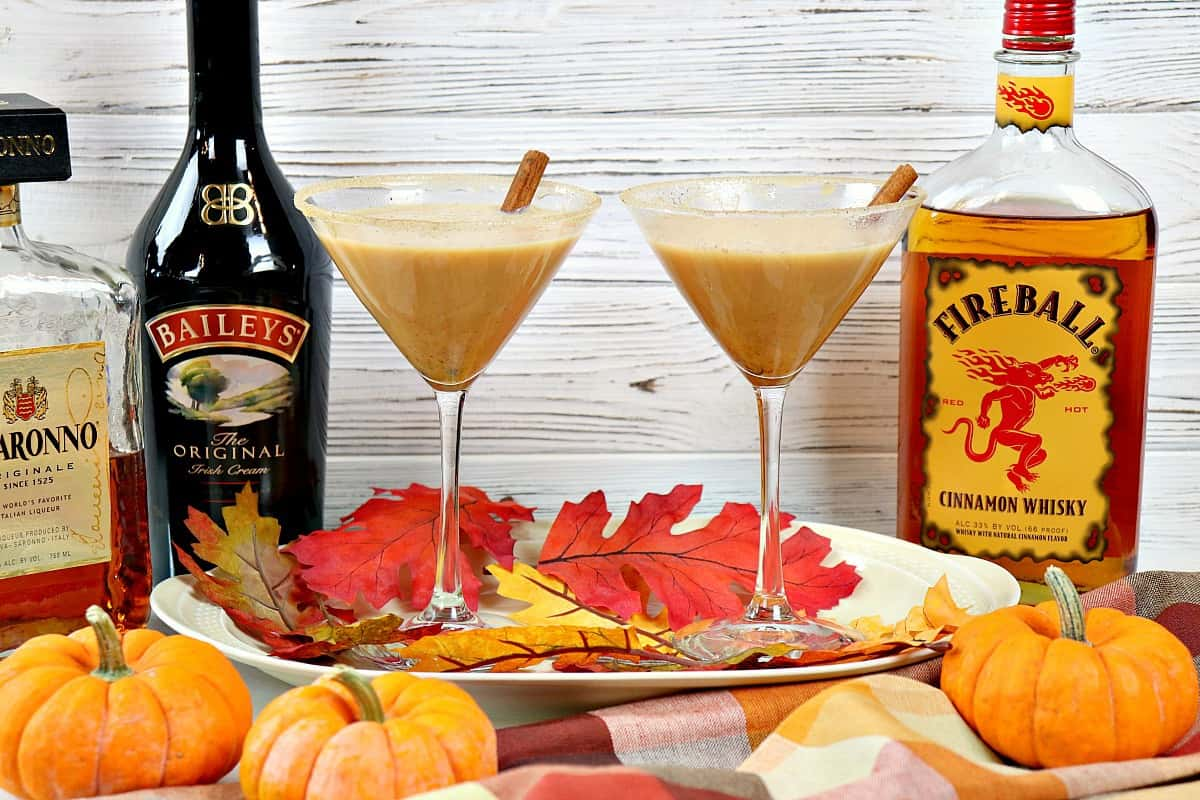 Two pumpkin spice martinis on a tray with pumpkins and leaves