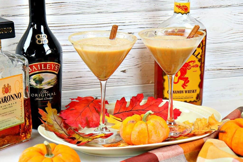 Two pumpkin spice martinis on an oval tray with leaves and pumpkins. Bottles of alcohol are in the background.