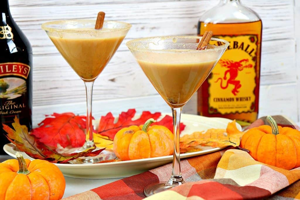 Two pumpkin spice martinis with a white wood background and a fall colored napkin and mini pumpkins.
