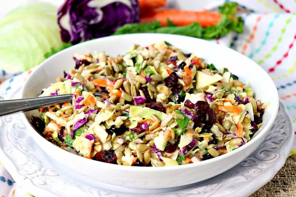 Colorful coleslaw in a white bowl with a spoon and a colorful napkin in the background.