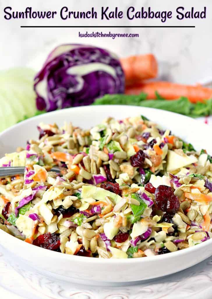 Colorful bowl of kale cabbage salad with purple cabbage and carrots in the background.