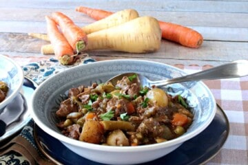 A horizontal photo of a hearty bowl of beef stew with carrots and parsnips in the background and a spoon in the bowl.