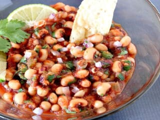 An offset bowl of Black-Eyed Pea Salsa with lime wedges and cilantro.