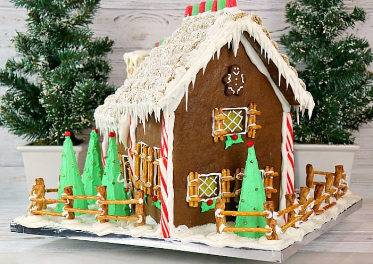 Side view of decorated gingerbread house with candy canes, gum drops, icicles, pretzel shutters, and mini wheat roof. - kudoskitchenbyrenee.com