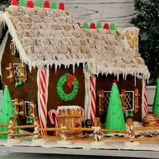 A fully decorated Gingerbread house complete with pretzel fence, candy cane pillars, and ice cream cone trees.