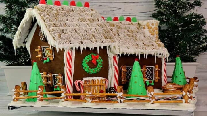 A cute decorated Gingerbread House Recipe and Tutorial using peppermint sticks, royal icing, pretzels, and gum drops.