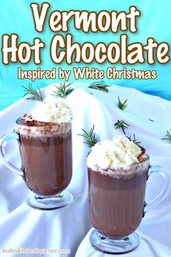A vertical photo of two mugs of Vermont Hot Chocolate on a snow covered mountain with a title text overlay graphic.