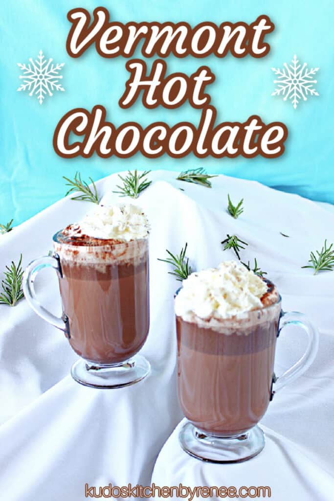 "Two mugs of Vermont Hot Chocolate on a ""snow covered"" mountain with blue sky and a title text overlay graphic"