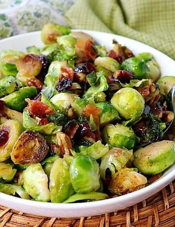Sauteed Brussels Sprouts in a white bowl with a spoon.