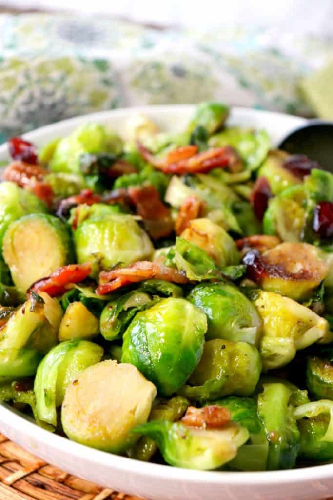 Closeup vertical image of sauteed Brussels sprouts with candied bacon.