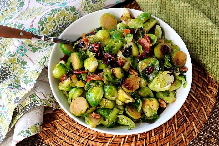 Sauteed Brussels sprouts in a white bowl on a rattan place mat and two napkins.