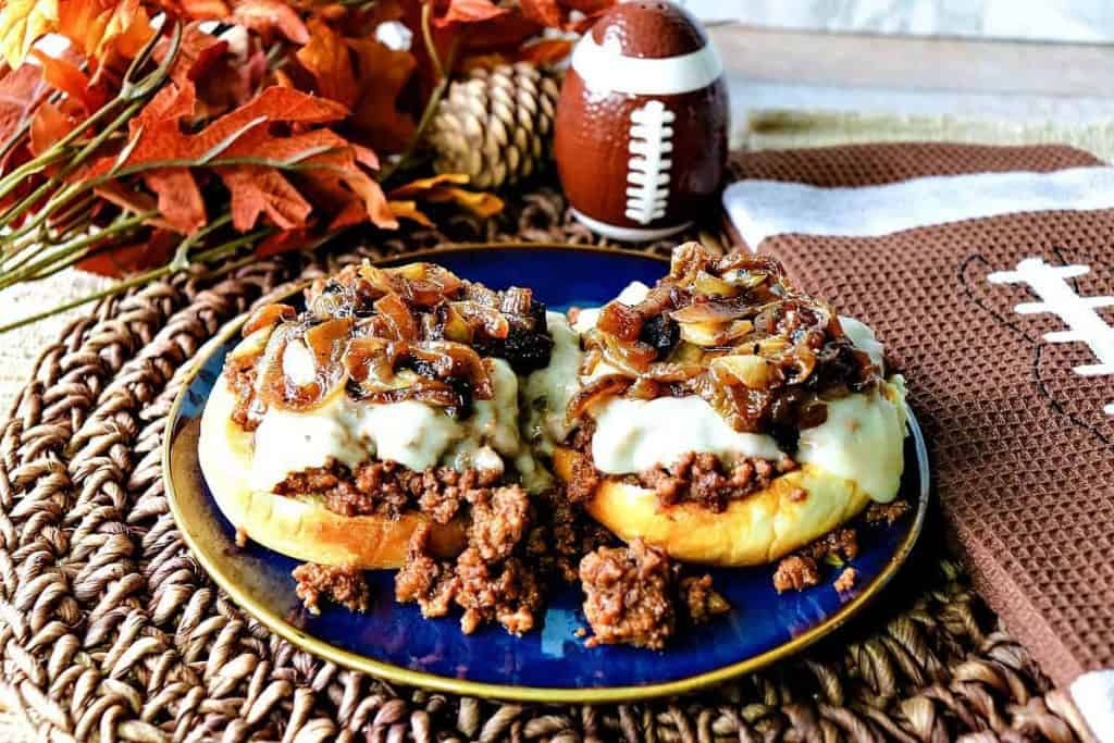 A open face sandwich of French Onion Sloppy Joes on a blue plate with melted cheese and caramelized onions.