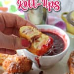 A hand holding a fried monte cristo appetizer roll-up dipped in raspberry jam