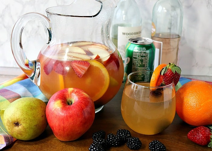 A pitcher filled with blackberry sangria with apples pears, strawberries and a glass.