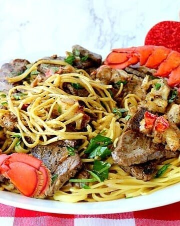 Steak and Lobster Linguine on a red and white check tablecloth. - Kudos Kitchen by Renee