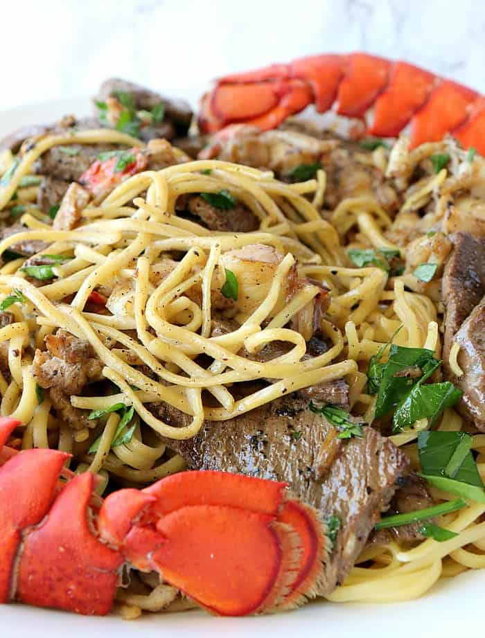 A closeup vertical image of linguine on a plate with lobster chunks and steak bites. A special occasion Valentine's dinner. Surf and turf pasta.