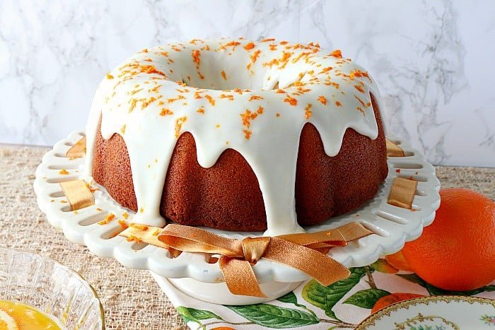 Citrus bundt cake with citrus icing and orange zest on a white cake plate.