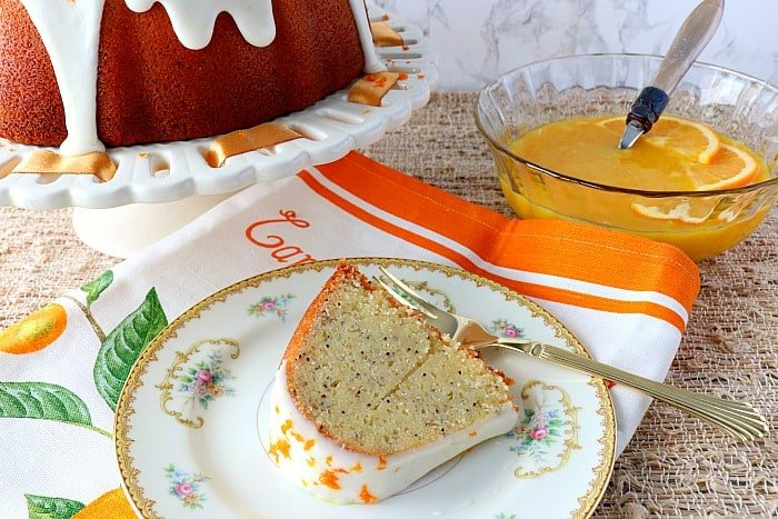 Slice of banana poppy seed orange bundt cake on a china plate with a fork and napkin.