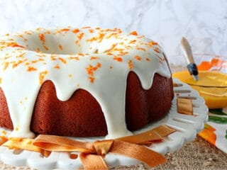 An Orange Bundt Cake on a cake stand with an orange ribbon and a bowl of orange curd in the background.