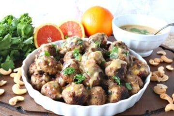 Turkey meatballs in a white dish with oranges and cilantro in the background