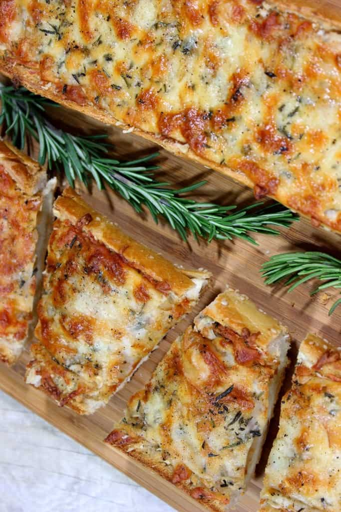 A closeup overhead vertical picture of garlic cheese bread for a BBQ side dish with golden melted cheese and fresh rosemary.