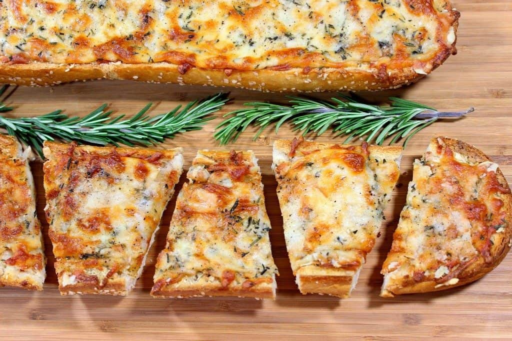 Two vertical halves of cheesy garlic bread and rosemary sprigs on a cutting board.
