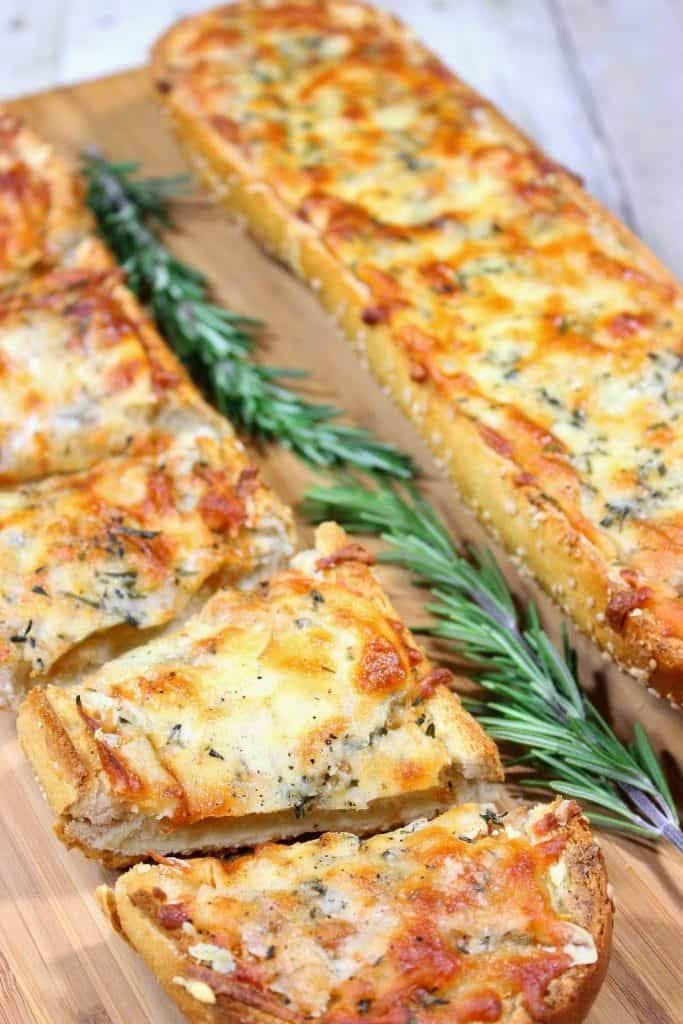 Two garlic cheese bread halves with rosemary sprigs on a cutting board.