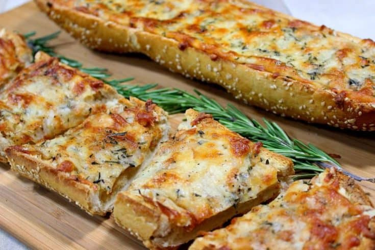 Sliced garlic cheese bread with rosemary spears on a cutting board.