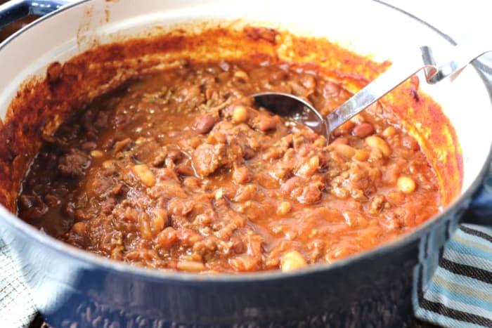 Pot of Microwave spaghetti squash chili with a ladle.