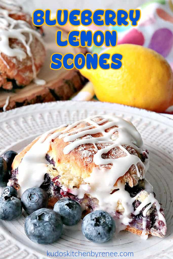 A vertical closeup image of a single Blueberry Lemon Scone on a white plate with fresh blueberries and a lemon in the background.