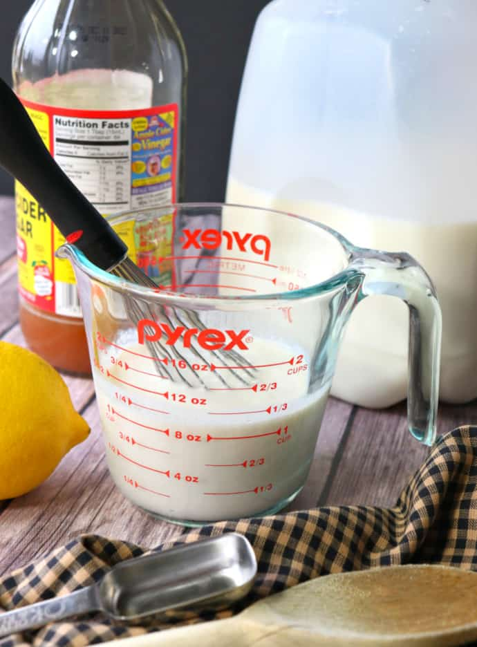 Vertical image of a measuring cup with buttermilk, whisk, vinegar, lemon, and milk in the background.