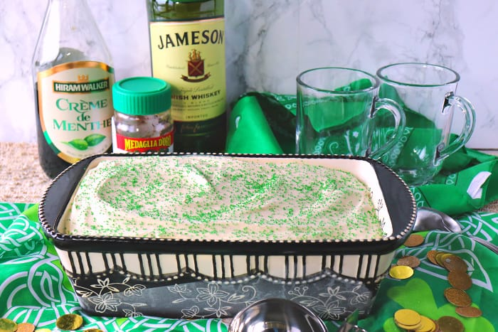 Frozen container of homemade no-churn Irish coffee ice cream with two empty glasses and bottles of Jameson and Creme de Menthe in the background.