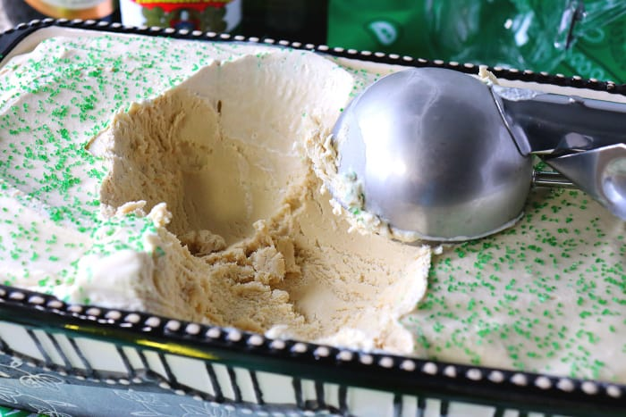 Closeup of a container of coffee mint ice cream with an ice cream scoop.
