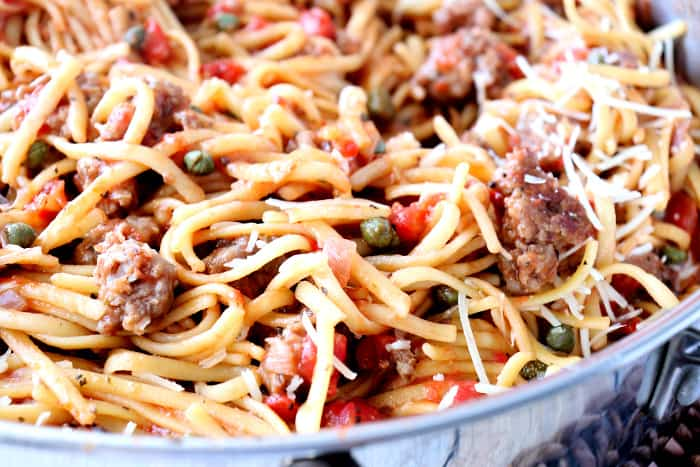 Closeup photo of linguine pasta with sausage, tomatoes, capers, and shredded Parmesan cheese.