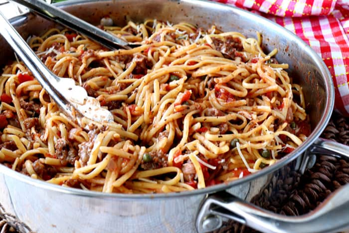 Pasta inside a large stainless steel pan with tongs and a red and white check napkin.
