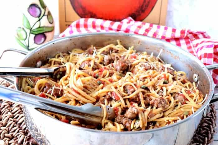 A horizontal photo of a skillet filled with one pot linguine with sausage and capers.