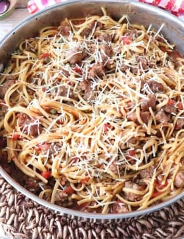 Overhead photo of a pan filled with pasta, sausage, and cheese with a red and white checked napkin.