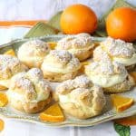 Plate of profiteroles with oranges and orange segments
