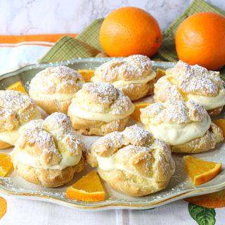 Plate of profiteroles with oranges and orange segments