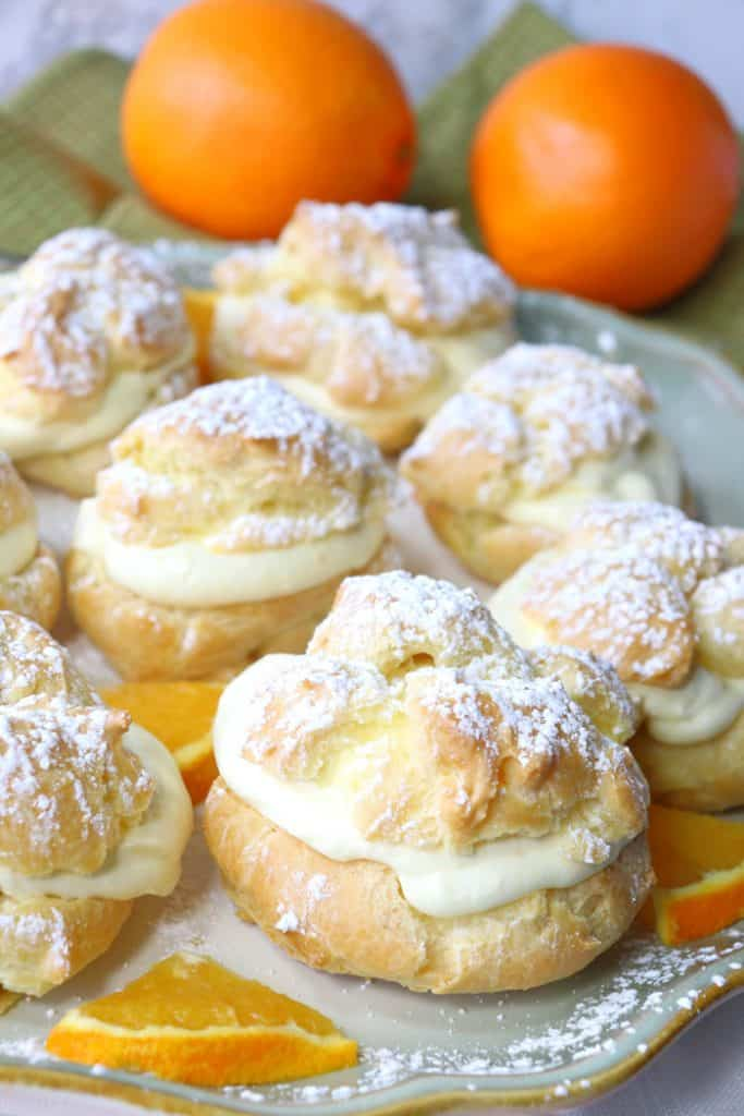 Vertical picture of a plate of orange eclairs with orange whipped cream. Valentine's dinner recipe roundup.