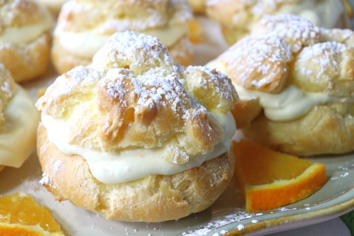 Closeup of profiterole filled with orange curd whipped cream and a confectioners sugar dusting