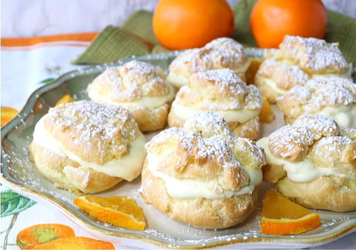 Golden filled eclairs on a plate with oranges and confectioners sugar