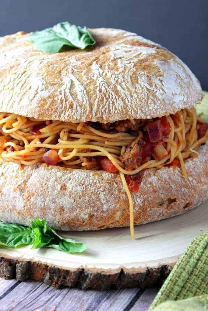 Vertical image of spaghetti stuffed into a round loaf of Italian garlic bread.