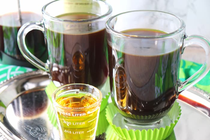 Two mugs of coffee on a silver tray with whiskey in a shot glass.