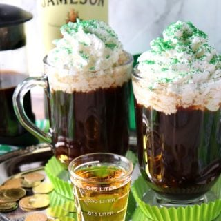 Two cups of Traditional Irish Coffee topped with whipped cream and green sugar.